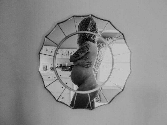A black and white capture of a nude pregnant woman reflected in a mirror.