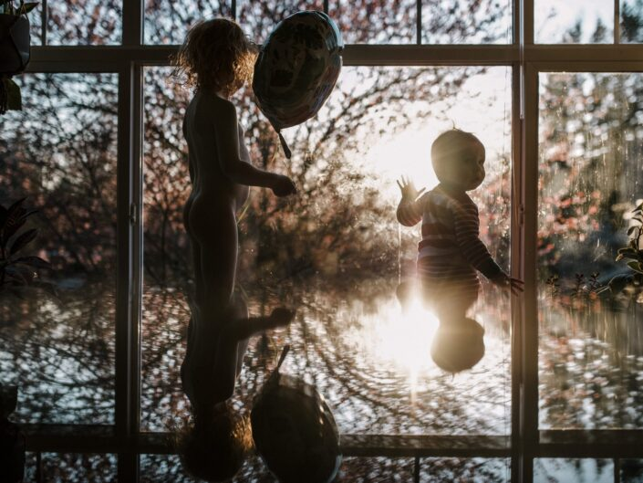 A reflection of two boys sitting in a window at sunset, one holds a balloon.